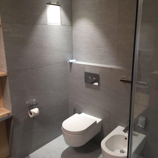 bagno in marmo e legno: sanitari e porte in vetro